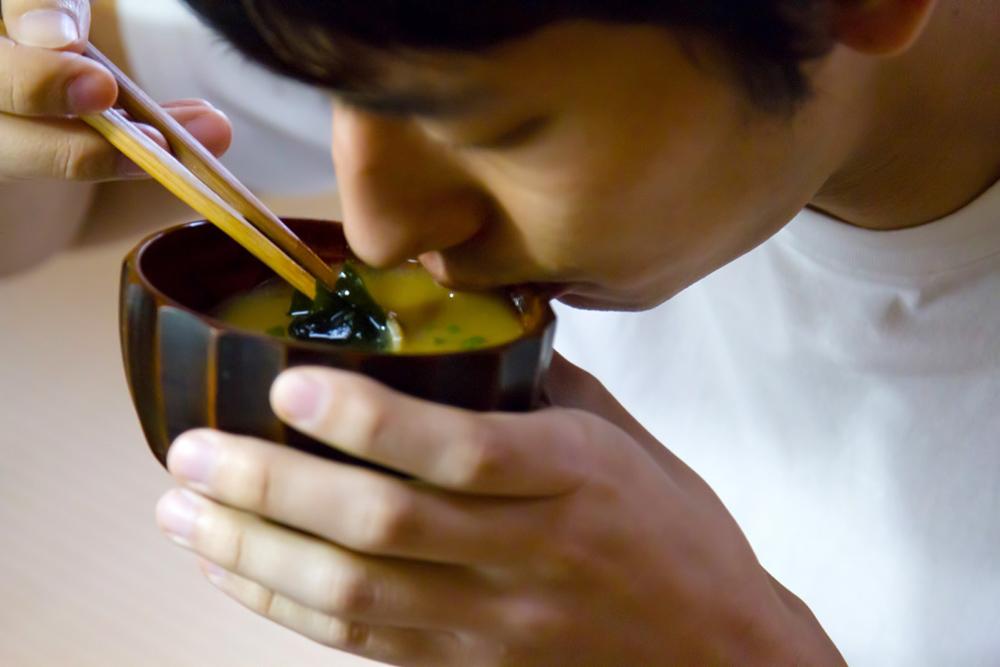 ワカメお味噌汁をすする男性