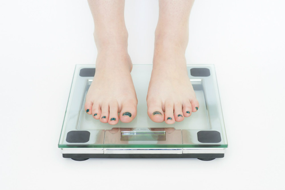 ダイエットで体重計に乗る女性の脚