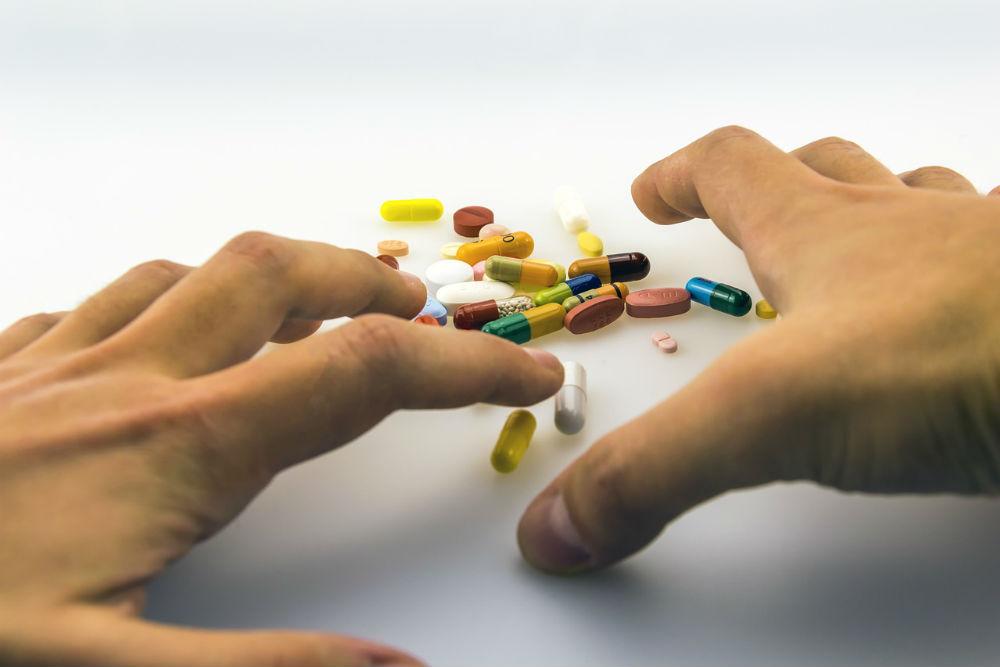 薬に手を伸ばす姿