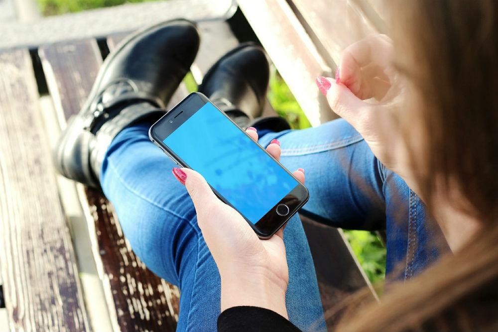 ベンチでスマートフォンを操作する人