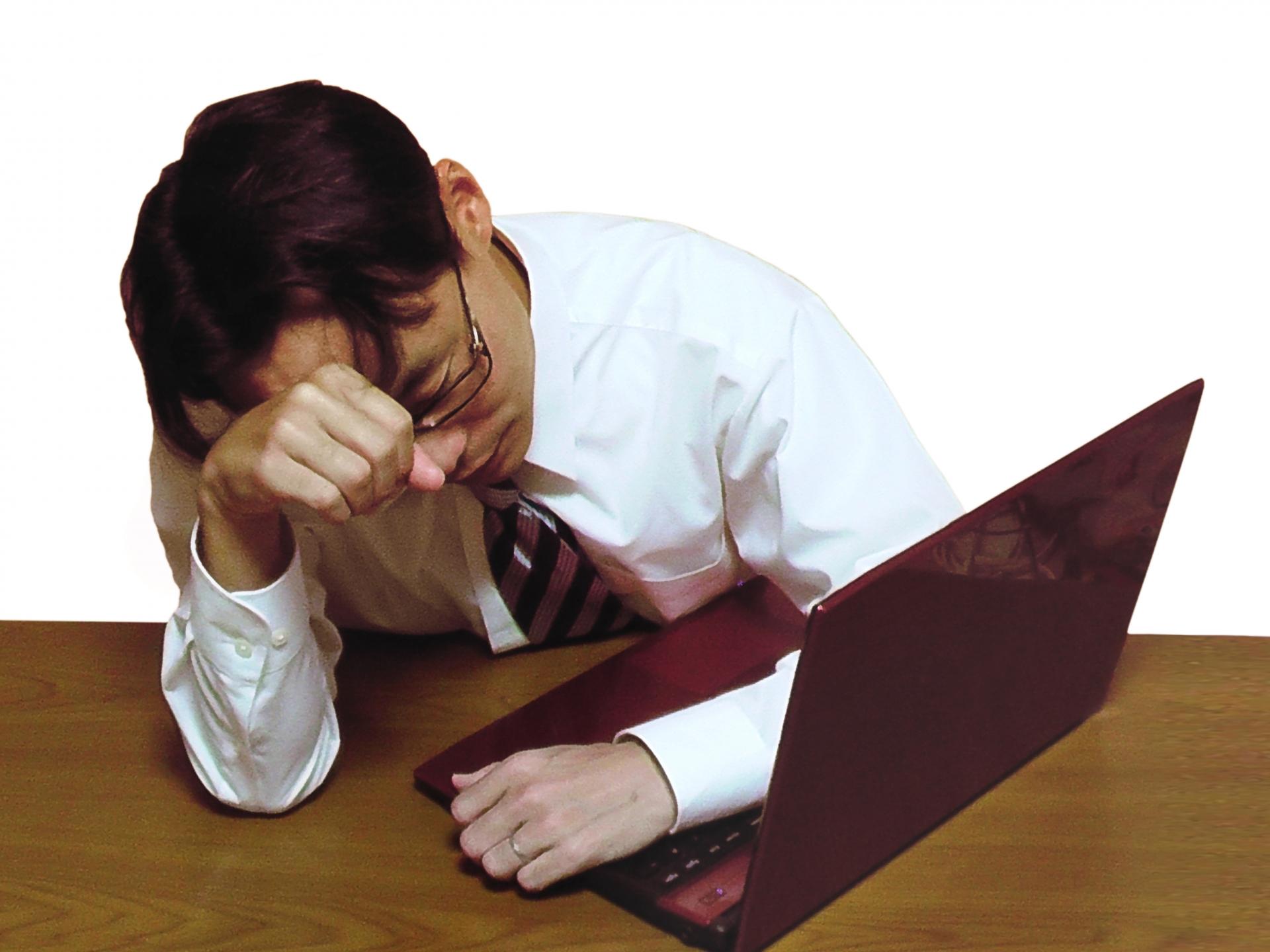 パソコンを前に頭が痛そうな男性